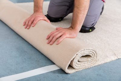 Close-up Of Worker's Hands Rolling Carpet for Installation At Home